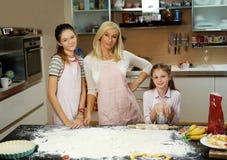 Γυναίκα και δύο κορίτσια στον πίνακα με τη ζύμη και τα μαγειρεύοντας εξαρτήματα Στοκ εικόνα με δικαίωμα ελεύθερης χρήσης