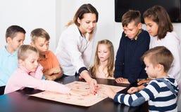 Γυναίκα και ευτυχή παιδιά που παίζουν το επιτραπέζιο παιχνίδι στοκ φωτογραφία με δικαίωμα ελεύθερης χρήσης