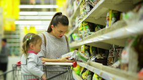 Γυναίκα και κορίτσι που επιλέγουν τα προϊόντα στην υπεραγορά Mom και κόρη μετά από να βάλει μερικά αγαθά στον περίπατο καλαθιών κ φιλμ μικρού μήκους