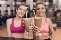 Γυναίκα και κορίτσι που πίνουν τα πρωτεϊνικά κουνήματα στη γυμναστική Φαίνονται ευτυχείς, μοντέρνοι και κατάλληλοι Στοκ Φωτογραφίες