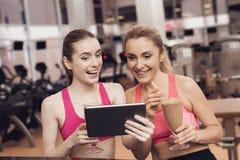 Γυναίκα και κορίτσι που πίνουν τα πρωτεϊνικά κουνήματα στη γυμναστική Φαίνονται ευτυχείς, μοντέρνοι και κατάλληλοι Στοκ Εικόνες