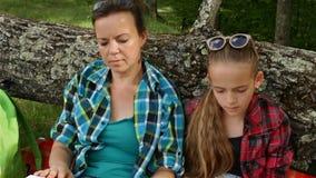 Γυναίκα και κορίτσι σε ένα πικ-νίκ που χαλαρώνει και που διαβάζει φιλμ μικρού μήκους