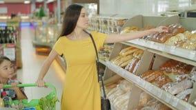 Γυναίκα και κόρη που αγοράζουν το φρέσκο ψωμί μέσα στο μανάβικο φιλμ μικρού μήκους