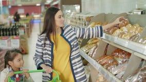 Γυναίκα και κόρη που αγοράζουν το φρέσκο ψωμί στην υπεραγορά απόθεμα βίντεο
