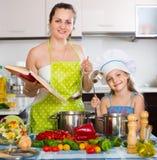 Γυναίκα και κόρη που προετοιμάζουν τα τρόφιμα που συμβουλεύονται το cookbook Στοκ Εικόνες