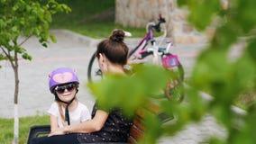 Γυναίκα και μικρό κορίτσι που στηρίζονται μετά από το γύρο ποδηλάτων απόθεμα βίντεο