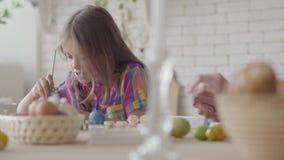 Γυναίκα και μικρό κορίτσι που χρωματίζουν τα αυγά Πάσχας με τα χρώματα και τη βούρτσα Προετοιμασία για τις διακοπές Πάσχας Μια ευ απόθεμα βίντεο