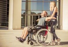 Γυναίκα και ο φίλος του στην έξοδο αναπηρικών καρεκλών Στοκ Εικόνα