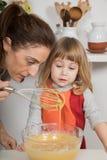 Γυναίκα και παιδί που εξετάζουν την κτυπημένη κρέμα Στοκ εικόνα με δικαίωμα ελεύθερης χρήσης