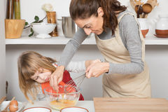 Γυναίκα και παιδί που μαγειρεύουν ανακατώνοντας ένα αυγό στο κύπελλο Στοκ φωτογραφίες με δικαίωμα ελεύθερης χρήσης