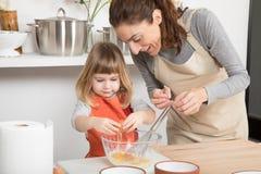Γυναίκα και παιδί που μαγειρεύουν σπάζοντας ένα αυγό στο κύπελλο Στοκ Εικόνες