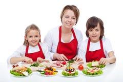 Γυναίκα και παιδιά που κατασκευάζουν τα δημιουργικά σάντουιτς πλασμάτων τροφίμων Στοκ εικόνες με δικαίωμα ελεύθερης χρήσης