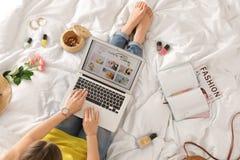 Γυναίκα και lap-top με το ανοικτό μαγείρεμα blog στο κρεβάτι στοκ εικόνες