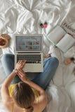 Γυναίκα και lap-top με το ανοικτό μαγείρεμα blog στο κρεβάτι στοκ φωτογραφίες
