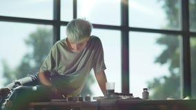 Γυναίκα καλλιτεχνών Hipster που εργάζεται στο ελαφρύ στούντιο με το μεγάλο πανοραμικό παράθυρο απόθεμα βίντεο