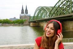Γυναίκα κασκών Smilling που ακούει τη μουσική με το ευρωπαϊκό τοπίο στο υπόβαθρο Πορτρέτο του όμορφου κοριτσιού με το διάσημο καθ Στοκ Φωτογραφία