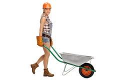 Γυναίκα κατασκευής που ωθεί wheelbarrow Στοκ φωτογραφία με δικαίωμα ελεύθερης χρήσης