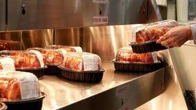 Γυναίκα κινήσεων που αγοράζει bbq το κοτόπουλο φιλμ μικρού μήκους