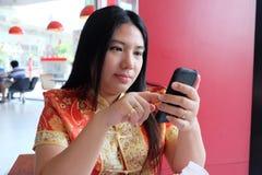 Γυναίκα, κινεζικό φόρεμα και κινητό τηλέφωνο Στοκ Εικόνα