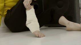 Γυναίκα κινηματογραφήσεων σε πρώτο πλάνο που επιδένει το πόδι της με τον ελαστικό επίδεσμο r Απροσδόκητο ζημία ή τέντωμα του αστρ στοκ φωτογραφίες