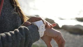 Γυναίκα κινηματογραφήσεων σε πρώτο πλάνο που χρησιμοποιεί το έξυπνο αθλητικό τρέχοντας ρολόι στην παραλία απόθεμα βίντεο
