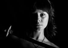 Γυναίκα κινηματογραφήσεων σε πρώτο πλάνο με το ξίφος στο σκοτεινό υπόβαθρο μαύρο λευκό Στοκ εικόνα με δικαίωμα ελεύθερης χρήσης