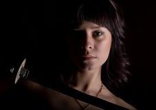 Γυναίκα κινηματογραφήσεων σε πρώτο πλάνο με το ξίφος στο σκοτεινό υπόβαθρο Στοκ Φωτογραφία