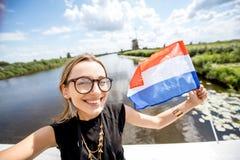 Γυναίκα κοντά στους παλαιούς ανεμόμυλους στις Κάτω Χώρες Στοκ Εικόνα