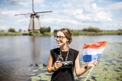 Γυναίκα κοντά στους παλαιούς ανεμόμυλους στις Κάτω Χώρες Στοκ εικόνες με δικαίωμα ελεύθερης χρήσης