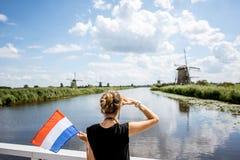 Γυναίκα κοντά στους παλαιούς ανεμόμυλους στις Κάτω Χώρες Στοκ εικόνα με δικαίωμα ελεύθερης χρήσης