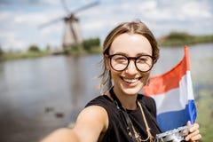 Γυναίκα κοντά στους παλαιούς ανεμόμυλους στις Κάτω Χώρες Στοκ Εικόνες
