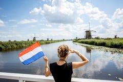Γυναίκα κοντά στους παλαιούς ανεμόμυλους στις Κάτω Χώρες Στοκ Φωτογραφία