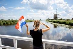 Γυναίκα κοντά στους παλαιούς ανεμόμυλους στις Κάτω Χώρες Στοκ φωτογραφίες με δικαίωμα ελεύθερης χρήσης