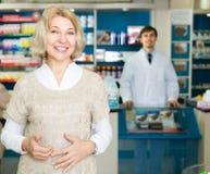 Γυναίκα κοντά στο μετρητή στο φαρμακείο στοκ φωτογραφίες