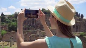Γυναίκα κοντά στο φόρουμ Romanum που παίρνει τη φωτογραφία στο κινητό τηλέφωνο Θηλυκός τουρίστας που παίρνει την εικόνα του ρωμαϊ φιλμ μικρού μήκους
