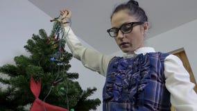 Γυναίκα κοντά στο χριστουγεννιάτικο δέντρο με τα φω'τα Χριστουγέννων φιλμ μικρού μήκους