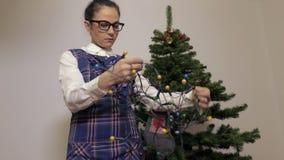 Γυναίκα κοντά στο χριστουγεννιάτικο δέντρο με τα φω'τα Χριστουγέννων απόθεμα βίντεο