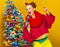 Γυναίκα κοντά στο χριστουγεννιάτικο δέντρο με το τραγούδι μικροφώνων Στοκ Φωτογραφία
