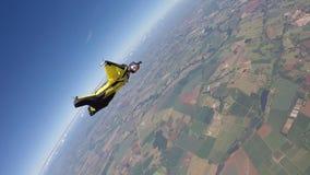 Γυναίκα κοστουμιών φτερών ελεύθερων πτώσεων με αλεξίπτωτο φιλμ μικρού μήκους