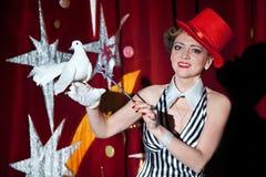 Γυναίκα μάγων τσίρκων που κρατά ένα άσπρο περιστέρι στο χέρι της Στοκ Εικόνες