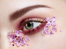 Γυναίκα ματιών makeup με ιώδη λουλούδια στοκ εικόνες