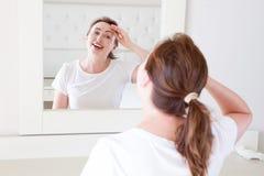 Γυναίκα Μεσαίωνα που κοιτάζει στον καθρέφτη στο μέτωπο ρυτίδων προσώπου στην κρεβατοκάμαρα Ρυτίδες και αντι έννοια φροντίδας δέρμ στοκ φωτογραφία με δικαίωμα ελεύθερης χρήσης