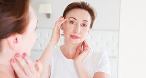 Γυναίκα Μεσαίωνα που κοιτάζει στον καθρέφτη στο πρόσωπο ρυτίδων στο μέτωπο Εμμηνόπαυση, ρυτίδες και αντι έννοια φροντίδας δέρματο στοκ εικόνα