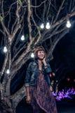 Γυναίκα μεταξύ των διακοσμητικών υπαίθριων φω'των σειράς που κρεμά στο δέντρο στο πάρκο στη νύχτα του Μπαλί όμορφη Ινδονησία νησι Στοκ εικόνα με δικαίωμα ελεύθερης χρήσης