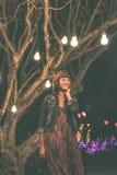Γυναίκα μεταξύ των διακοσμητικών υπαίθριων φω'των σειράς που κρεμά στο δέντρο στο πάρκο στη νύχτα του Μπαλί όμορφη Ινδονησία νησι Στοκ Φωτογραφίες