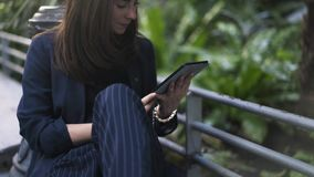 Γυναίκα με έναν υπολογιστή ταμπλετών στο βοτανικό κήπο στο σταθμό τρένου Atocha, Μαδρίτη απόθεμα βίντεο