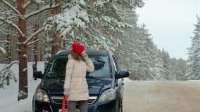 Γυναίκα με ένα αυτοκίνητο αχύρου στο δρόμο το χειμώνα φιλμ μικρού μήκους
