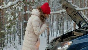 Γυναίκα με ένα αυτοκίνητο αχύρου στο δρόμο το χειμώνα απόθεμα βίντεο