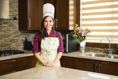 Γυναίκα με ένα καπέλο αρχιμαγείρων ` s στην κουζίνα Στοκ Εικόνα