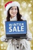 Γυναίκα με ένα κείμενο χειμερινής πώλησης και ένα υπόβαθρο Χριστουγέννων Στοκ Εικόνα